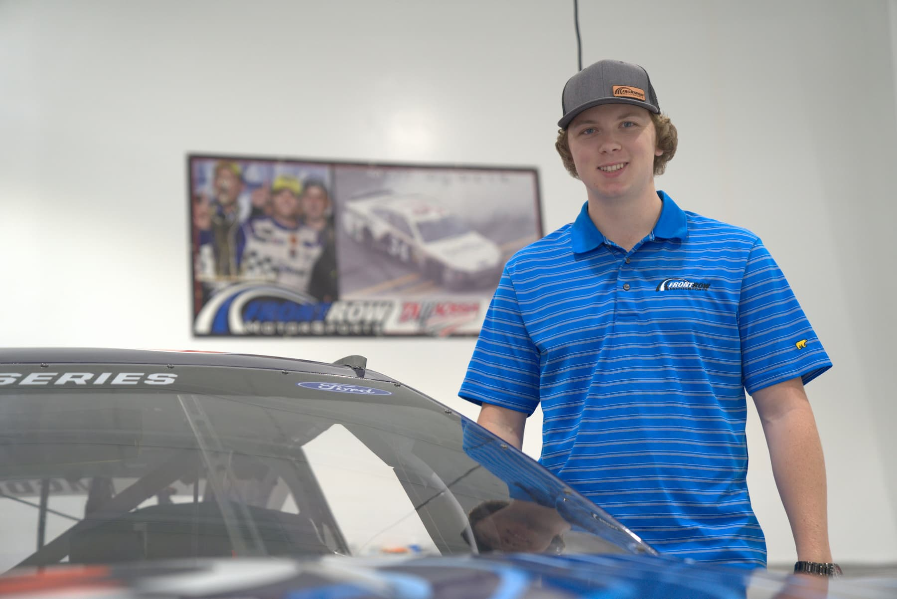 Mac MacLeod poses next to a NASCAR Cup Series racecar at Front Row Motorsports. Photo courtesy of LakeSide Media.