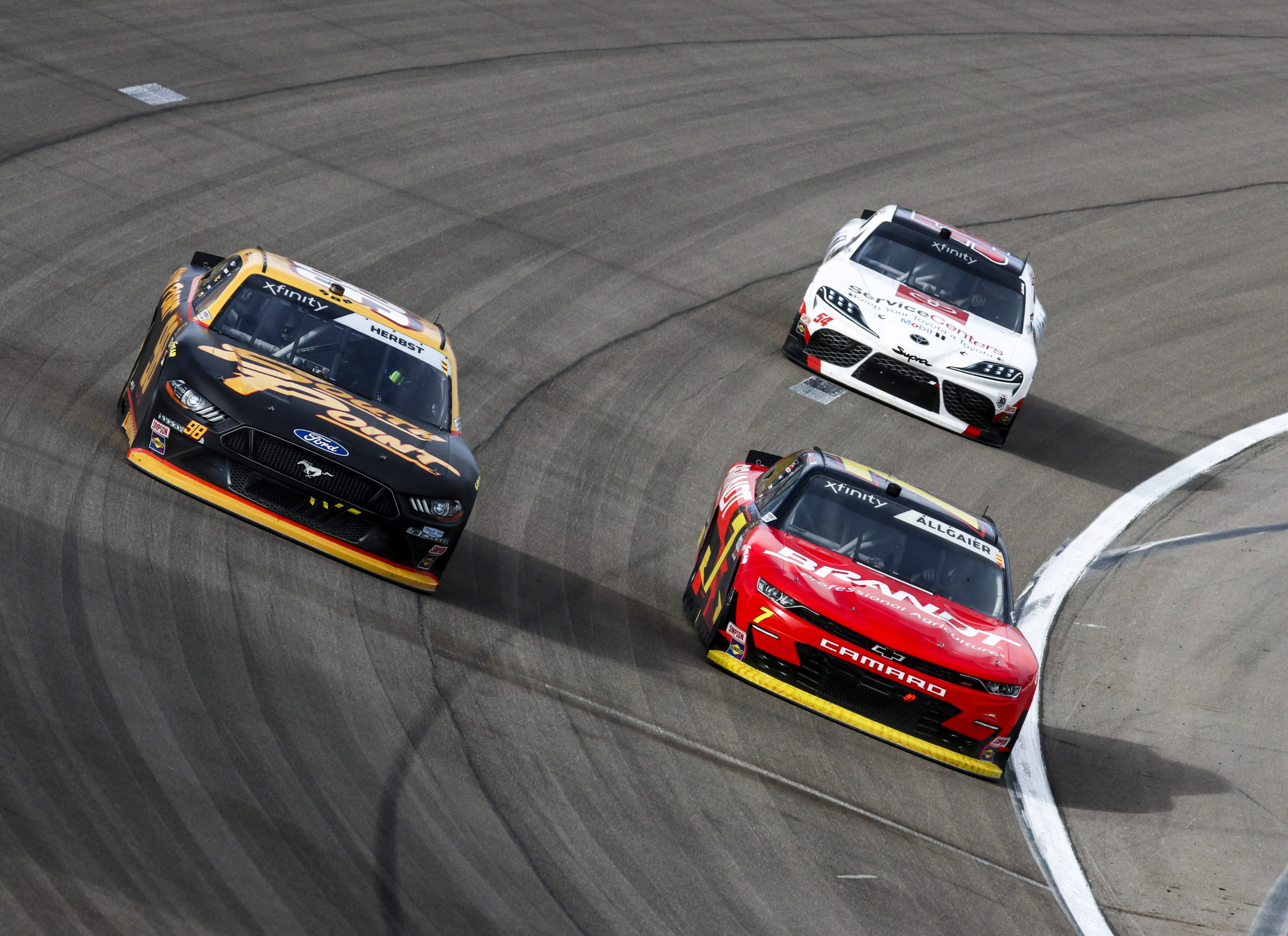 Riley Herbst battles on the outside of Justin Allgiaer ahead of Ty Dillon in the 2021 Alsco Uniforms 300 at Las Vegas Motor Speedway. Photo by Rachel Schuoler / Kickin' the Tires.