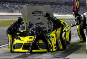 Brandon Jones sits on pit road at Daytona International Speedway. The No. 19 crew works under the hood to address an overheating issue after debris covered the front grill.
